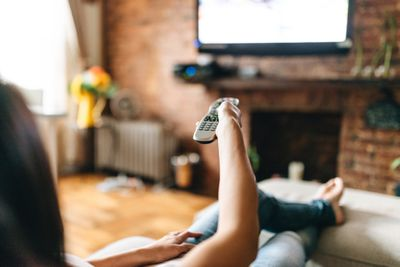 Woman using TV remote