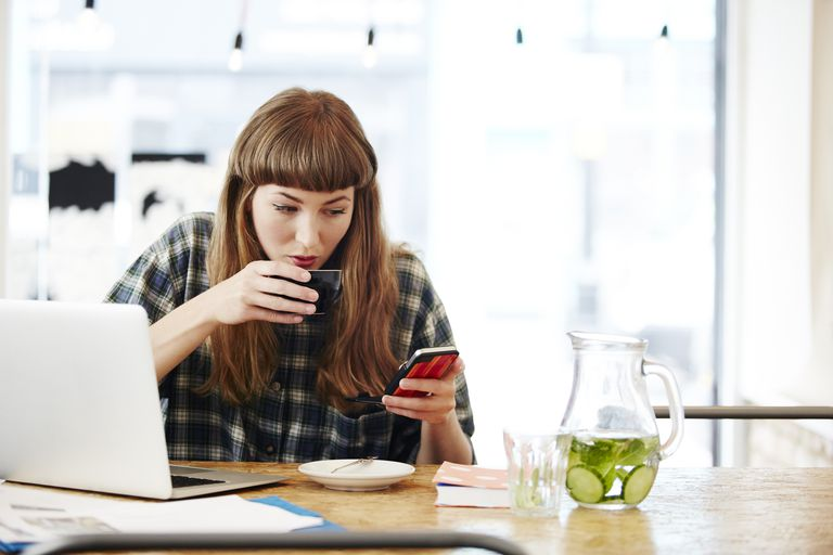 woman with smartphone and laptop drinking tea