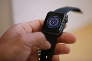 A hand holding an Apple Watch with the startup icon on the screen
