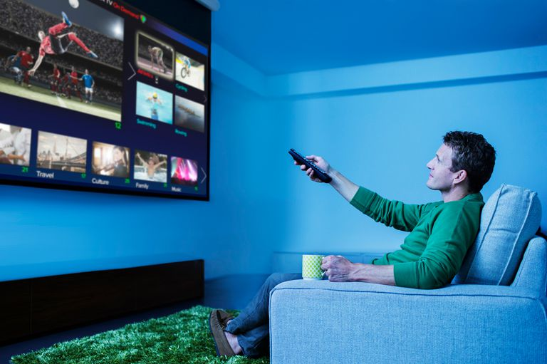 Man watching TV using remote control