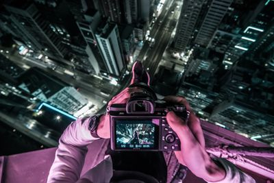 Midsection Of Man Photographing Illuminated Cityscape At Night from the top of a tall building