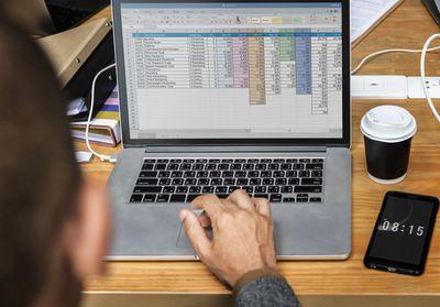 Businessman working on laptop spreadsheet