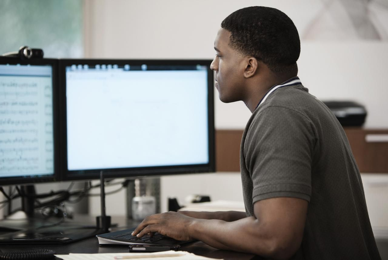 A person working at a Windows computer with dual monitors.