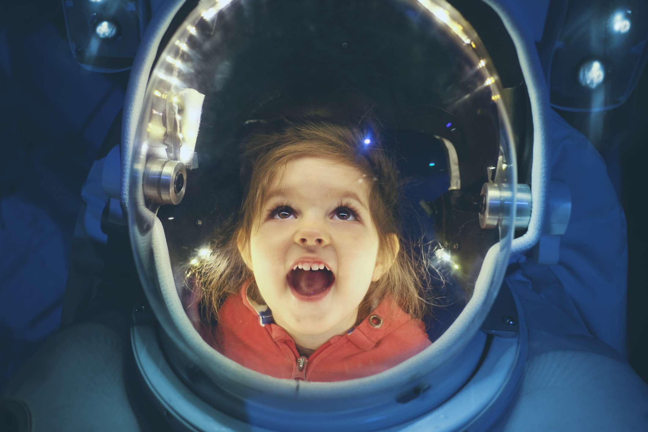 Small girl enjoying being inside of astronaut suit