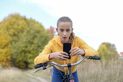 Girl riding her bike and looking at her iPhone in shock