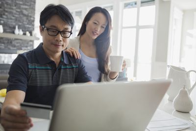 A couple with credit card at laptop