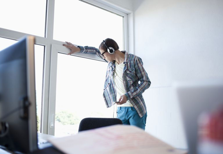 young office worker listening to music at window