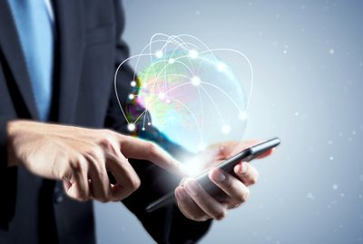 A man touching an iPhone screen with a CGI rendering of a cellphone network signal showing above it.