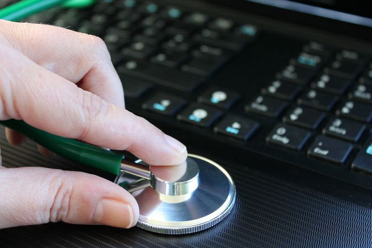 Laptop with someone holding a stethoscope to it.