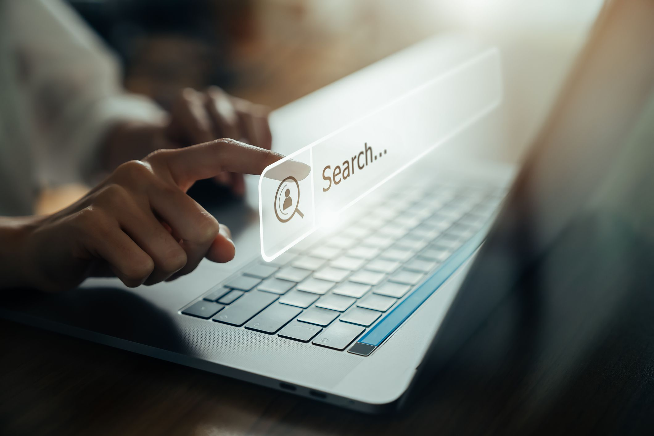 Closeup of someone using a laptop and touching a virtual searchbar overlayed on the image.