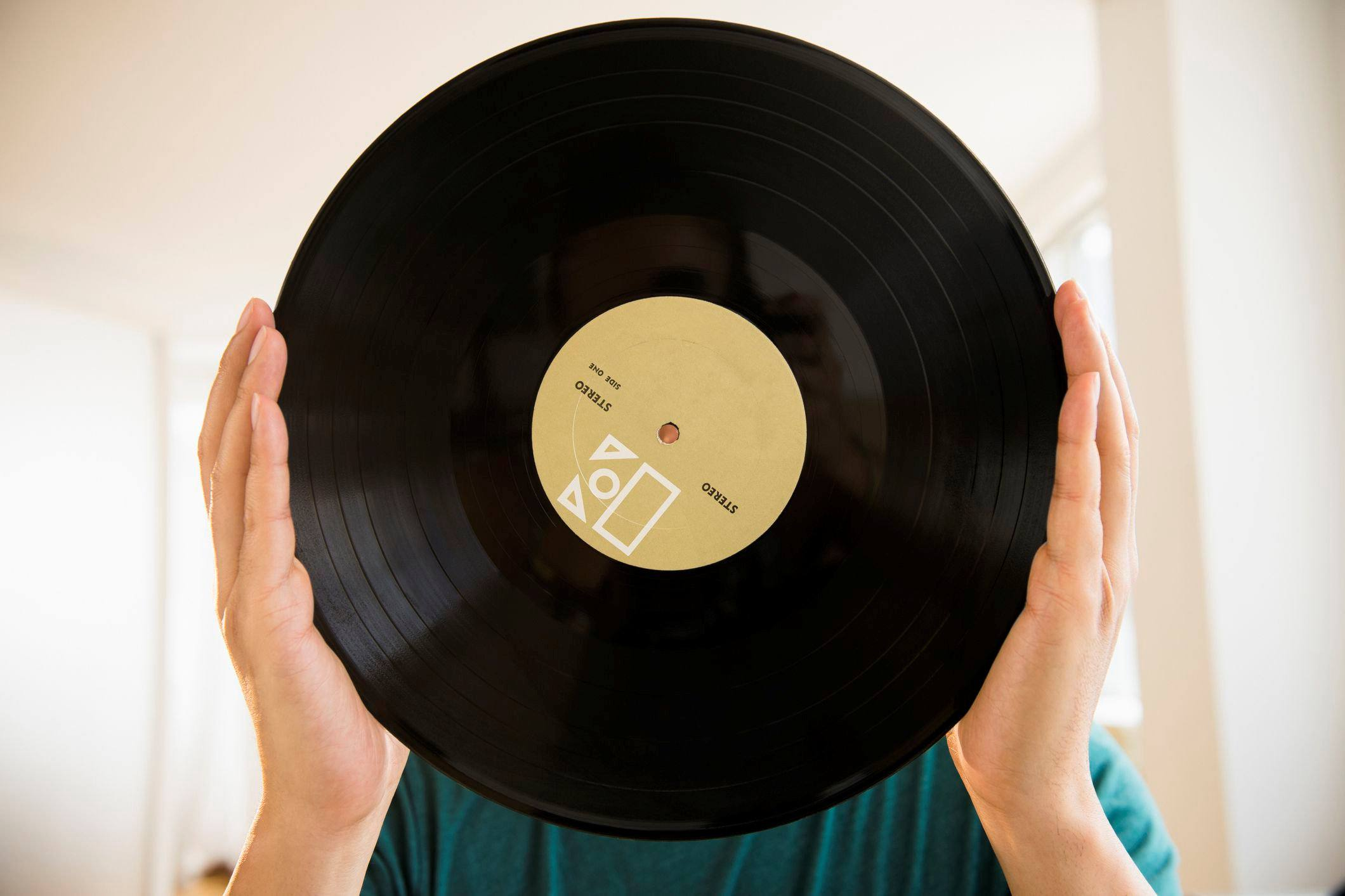 hands holding up a vinyl record
