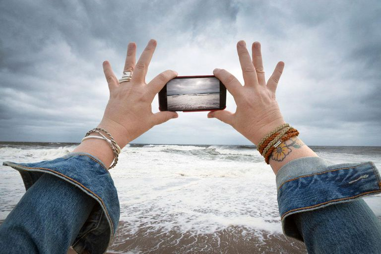 Woman taking photo on phone on a stormy beach