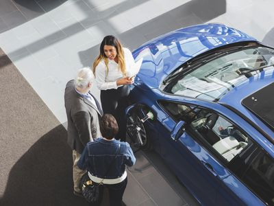 A female car salesmen standing next to two electric vehicle shoppers