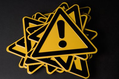 Stack of warning signs that are yellow triangles