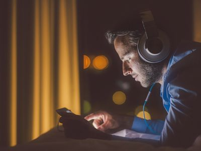 A person listens to music with headphones on a tablet.