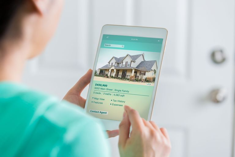 An image of a woman looking at a real estate listing on a tablet.