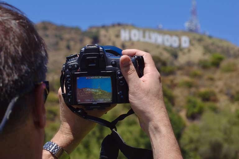 A man taking photos of the Hollywood sign with a DSLR camera.