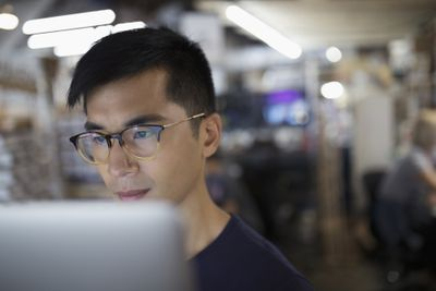 Focused male engineer working at laptop