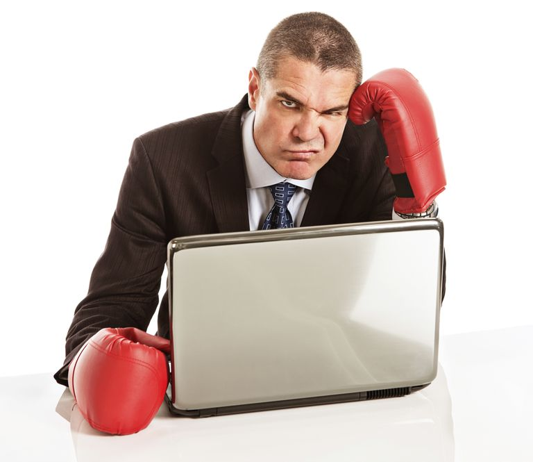 Frustrated fed-up businessman in boxing gloves with laptop