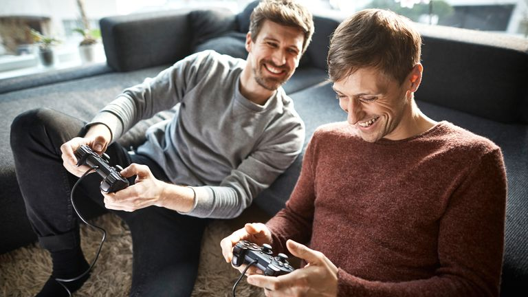 Two men playing an offline local multiplayer video game on their PlayStation 4 console.