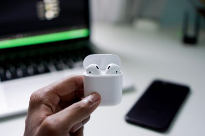 Someone holding AirPods in a case with a smartphone and computer in the background.