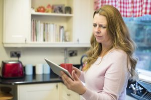 woman in kitchen looking at tablet with a confused look.