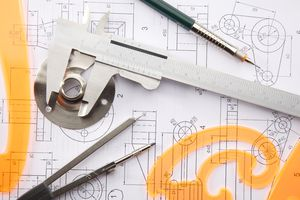 A set of calipers on architectural blueprints