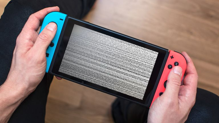 A man holding a frozen Nintendo Switch console with static on its screen.