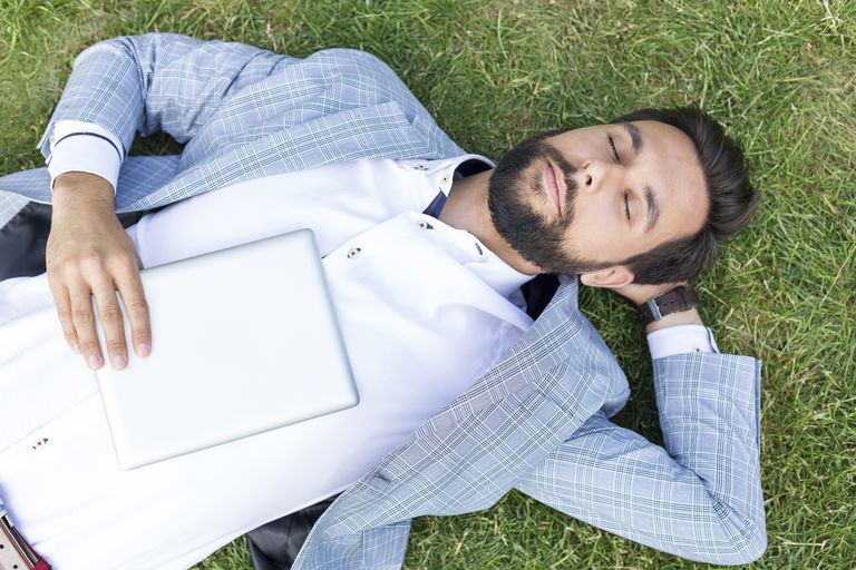 Man lying on lawn with closed eyes holding digital tablet