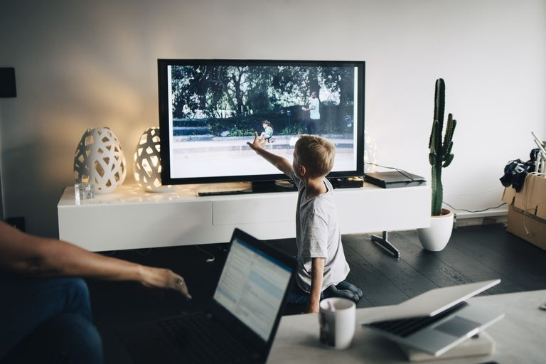 Boy kneeling while touching smart TV
