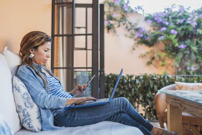 Woman working with phone and laptop on sofa