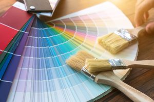 Paint chips and paint brushes are spread out on a table.