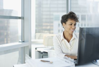 A business woman is working at a computer and smiling.