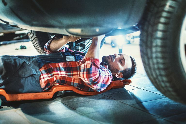 A man working underneath a car.