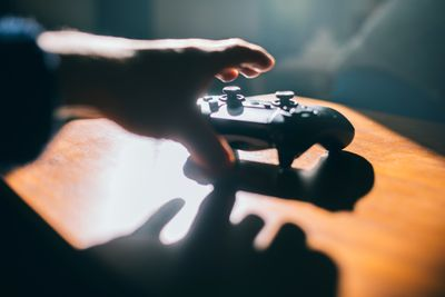 Closeup of a hand reaching for a gaming controller.