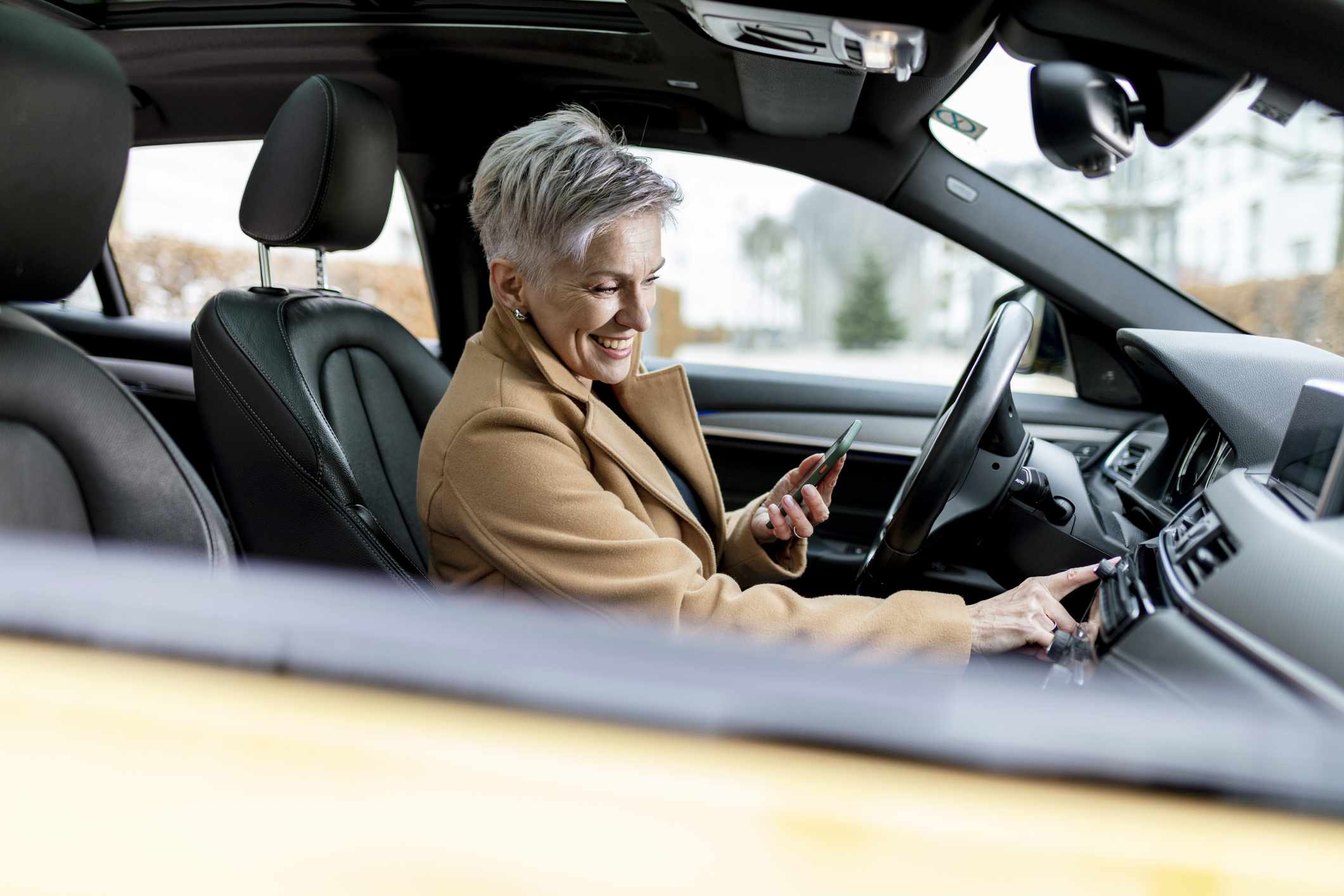 Woman with smartphone in car