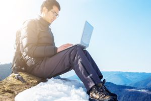 Man using laptop at mountain practicing tips for keeping a laptop safe in cold weather