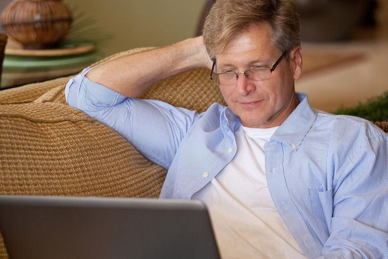 Man sitting on couch looking at laptop computer