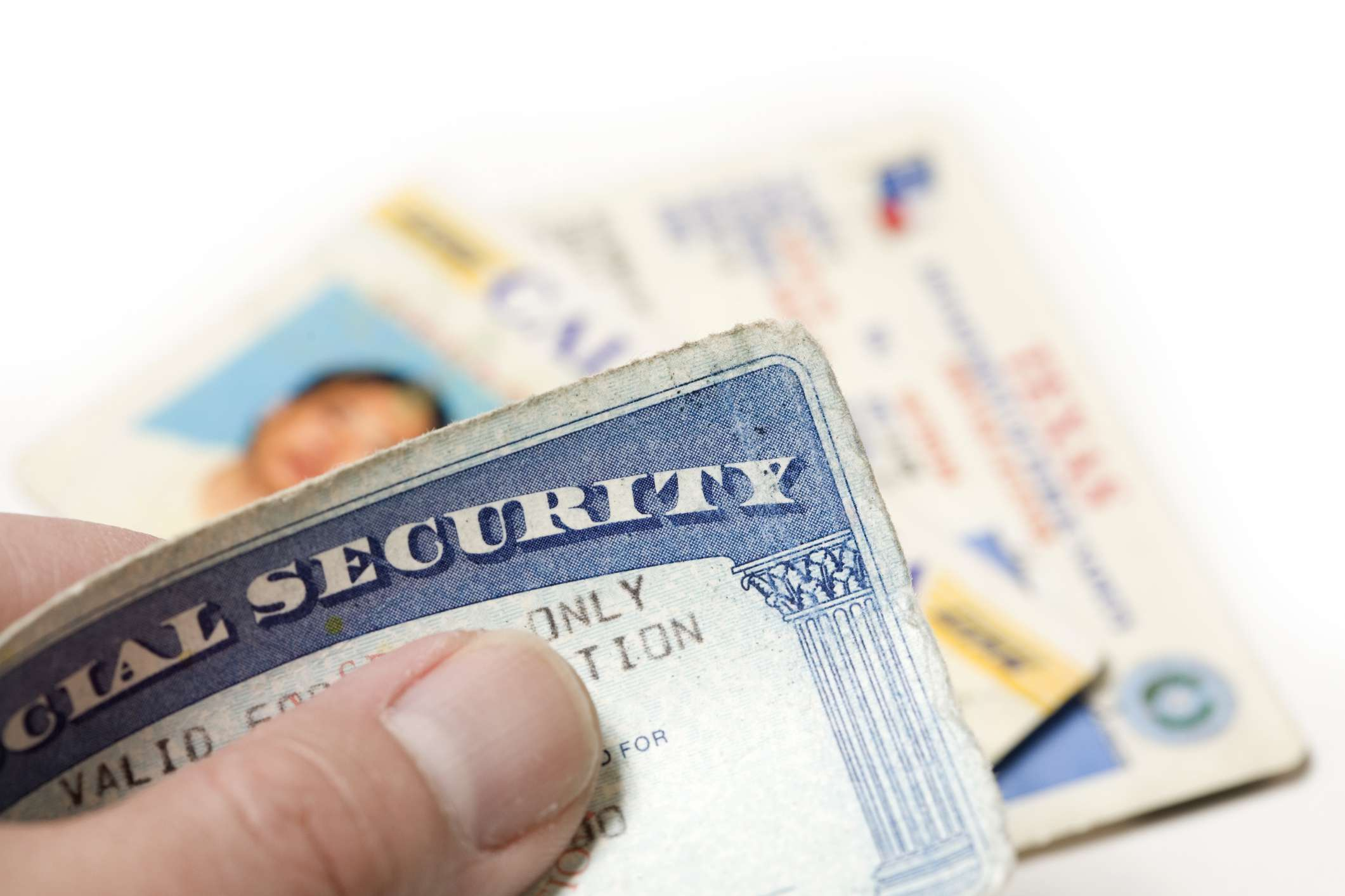 studio shot of hand holding social security card