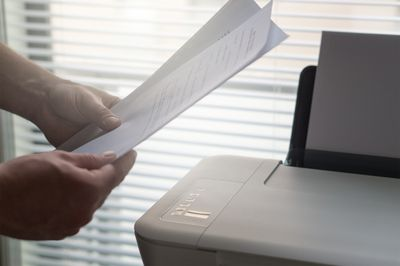 Hands holding documents above an at home printer