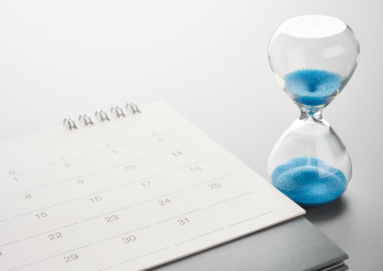 A sand timer and a calendar sitting on a desk.