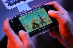 Hands holding and playing a combat game on PSP