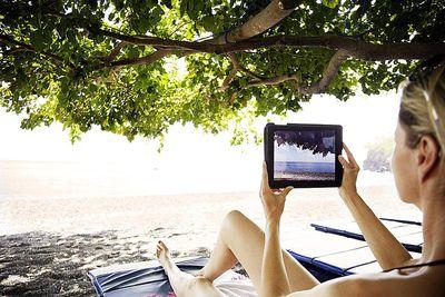 woamn making a photo with an iPad at the beach