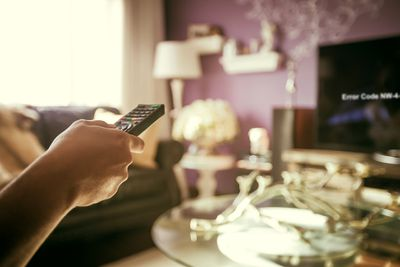 A woman pointing a remote at a TV showing the Netflix NW-4-7 error code.