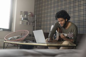 Man playing guitar and watching YouTube