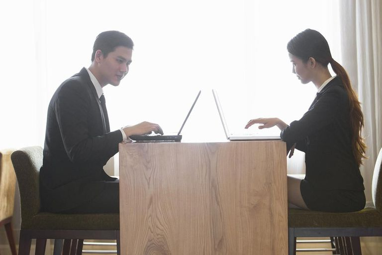 two people with laptops sharing files