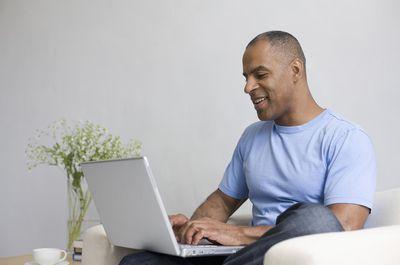 Mature man typing on laptop