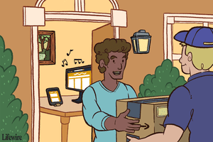 Person getting an Amazon box at their front door with a computer and Kindle on the table behind them
