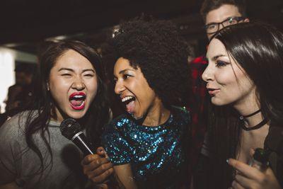 Woman holding karaoke microphone for singing friend
