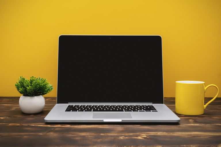 Photo of open Mac laptop in front of a yellow wall